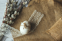 Flat Lay Composition Of Easter Egg And A Bouquet Of Willow Branches On A Background Of Burlap And White Wooden Background, Space For Text. Happy Easter Spring Festive Greeting Card.