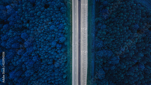Obraz Aerial View Of Highway Road Through Blue Forest Landscaper.Toned Photo. Top View Flat View Of Highway Motorway Freeway From High Attitude. Trip And Travel Concept - fototapety do salonu
