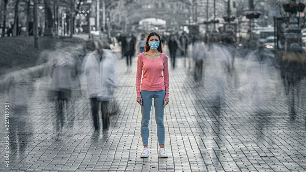Fototapeta The young woman with medical mask on her face stands on the crowded street