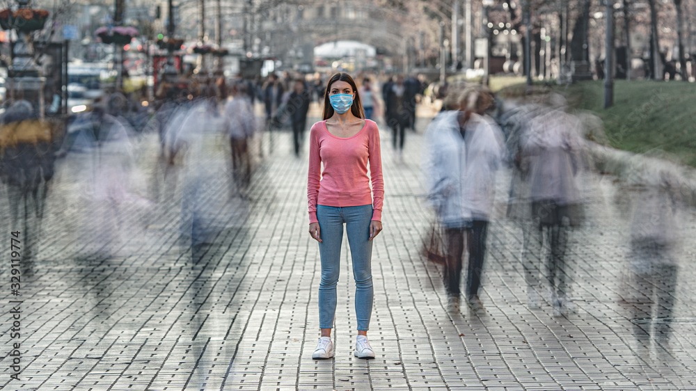 Fototapeta The woman with medical face mask stands on the crowded street