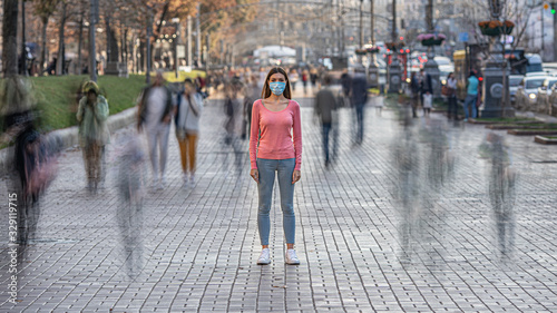 Obraz The woman with medical face mask stands on the crowded street - fototapety do salonu