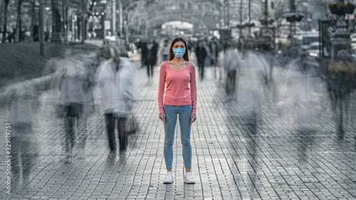 Obraz The young woman with medical mask on her face stands on the crowded street - fototapety do salonu