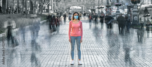 Fototapeta The young woman with medical mask on her face stands on the crowded street obraz