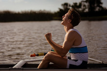 Side View Of Happy Young Man Sitting In Rowing Boat