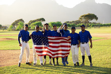 Portrait Of Baseball Players Standing With American Flag In Field