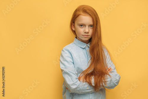 portrait of caucasian sad red haired girl isolated over yellow background Canvas Print