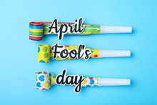 Party Horns With Words APRIL FOOL'S DAY On Light Blue Background, Flat Lay