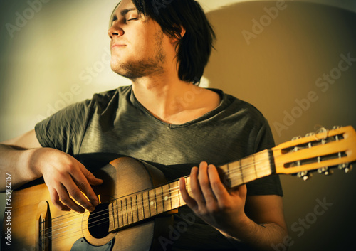 Fotografie, Obraz A handsome brunette with a stubble on his face and a dark t-shirt is happy to play an old acoustic guitar, illuminated by bright sunlight