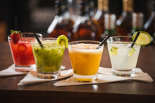 Passion Fruit,  Kiwi Lemon, Strawberry Caipirinhas, Decorated With Cherry On A Wooden Table