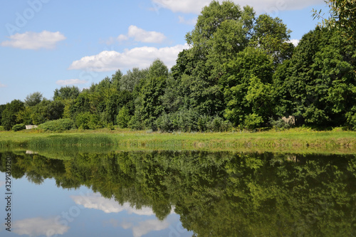 Fototapeta Reflection of white clouds and forest in a river or lake on a sunny day, nature. obraz na płótnie