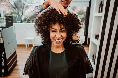 Photo Beautiful latin woman with short curly brown hair getting a treat at the hairdresser