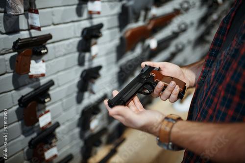 Man holds handgun in gun shop Wallpaper Mural