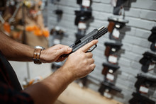 Man Choosing New Handgun In Gu...