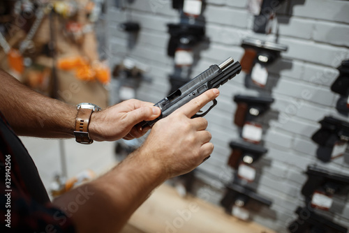 Man choosing new handgun in gun shop Wallpaper Mural