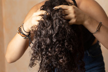 Young Woman With Long Curly Hair Giving Herself A Scalp Massage As Part Of Her Haircare Routine