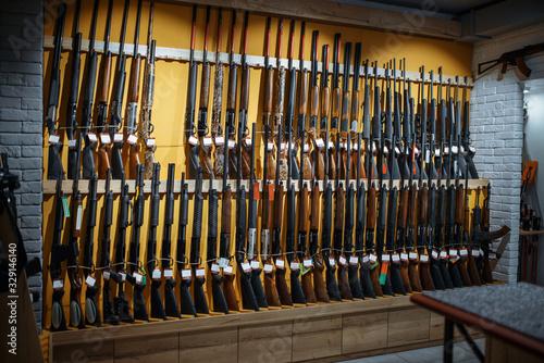 Photo Rows of rifles on the wall, showcase in gun shop