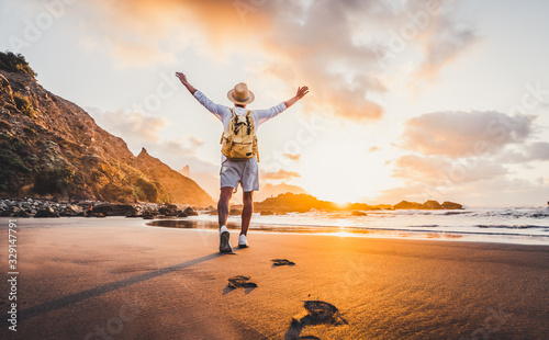 Obraz Young man arms outstretched by the sea at sunrise enjoying freedom and life, people travel wellbeing concept - fototapety do salonu