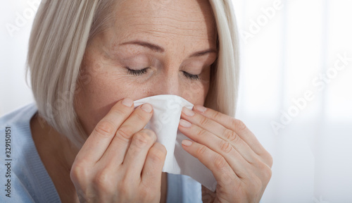 Fototapeta Healthcare, cold, allergy and people concept, sick woman blowing her runny nose