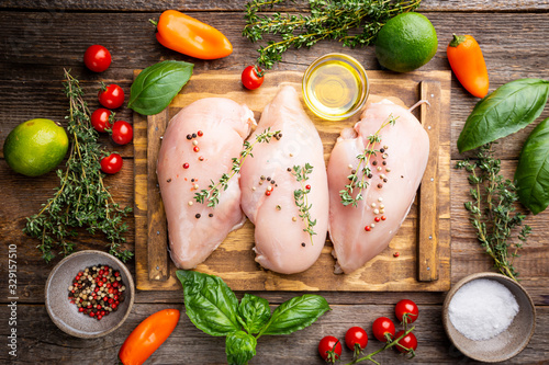 Foto Fresh raw chicken breast with herbs and spices, top view