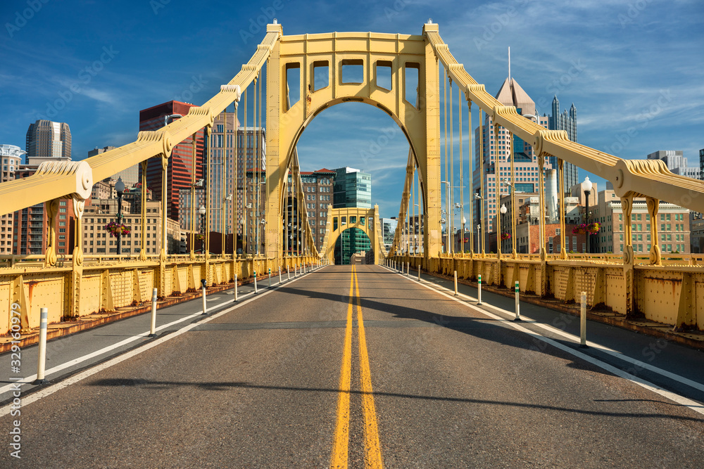 Fototapeta Traffic and people cross the Allegheny River on the Roberto Clemente Bridge in downtown Pittsburgh Pennsylvania USA