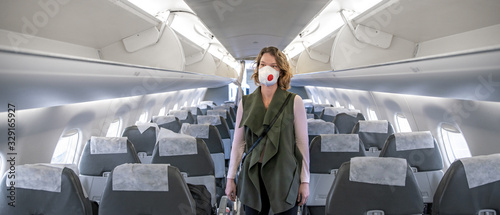 Obraz woman on board of aircraft with respirator on head. protect themselves against viral disease. People cancel travel abroad due to coronavirus - fototapety do salonu