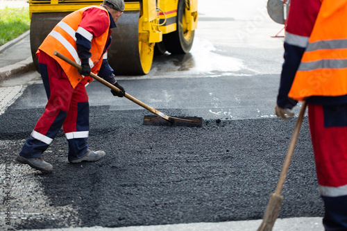 Fotografie, Obraz The road workers' working group updates part of the road with fresh hot asphalt and smoothes it for repair