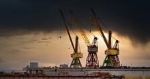 Massive Blue, Orange And Yellow Cranes In Harbour