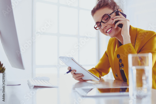 Portrait of beautiful woman making call while sitting at her workplace in front of laptop and working on new project