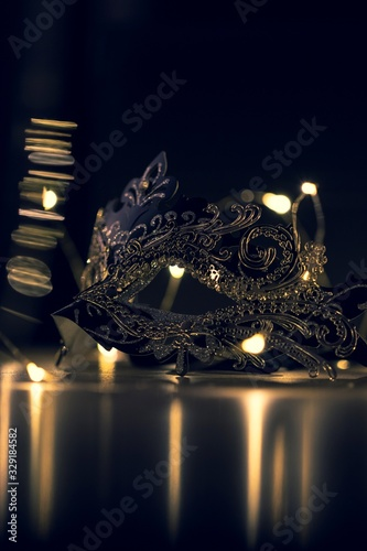 Fototapeta A portrait of a venetian mask full of mystery on a wooden table surrounded by lights and their reflection. It is perfect to hide someones identity. obraz na płótnie