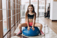 Charming Little Girl Sitting On Ball In Fitness Hall