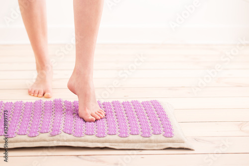 Woman stanfing on acupressure mat. Home massage. Canvas Print