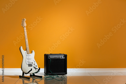 Photo Modern guitar and amplifier near color wall