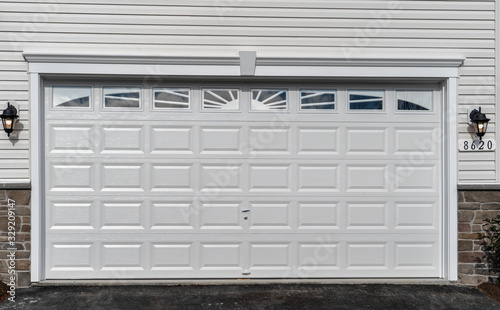 Obraz na plátne Double car classic insulated steel raised panel garage door framed with a white