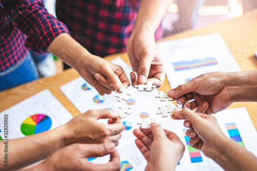 Fotomural employees standing around in a circle holding jigsaw pieces each matching it against one another, representing teamwork problem solving, help and support within small businesses or company