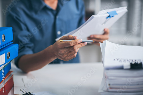Photo Young business man doing financial reports feeling stress with stack of papers
