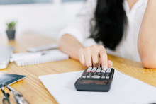 Asian Woman Entrepreneur Using A Calculator Calculating Financial Expense At Home Office, Press Calculator Button Finance Analyzing  E-payment Technology, Shopaholic Lifestyle, Mobile Application