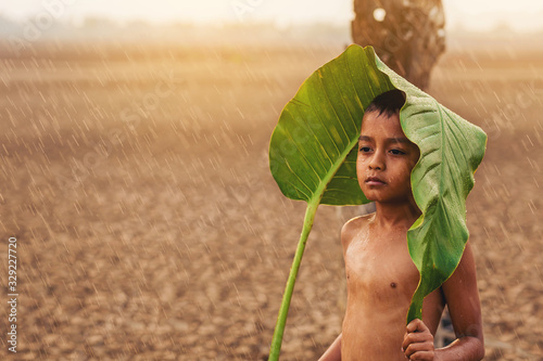 Fotomural Climate change, Asian boys waiting for something with first falling rain season on dry cracked land