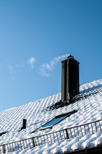 Roof In Winter With Snow Guard And Smoking Chimney