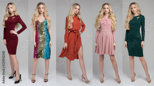 Obraz Attractive young blonde model posing in trendy dress isolated at white studio background. Beautiful girl standing in trendy clothing looking at camera - fototapety do salonu