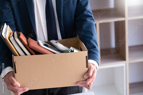 Sad Fired Young Employee businessmen hold boxes including pot plant and documents for personal belongings unemployment, resigned concept.