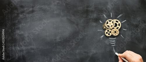 Obraz Education concept image. Creative idea and innovation. Wooden gears light bulb metaphor over blackboard - fototapety do salonu