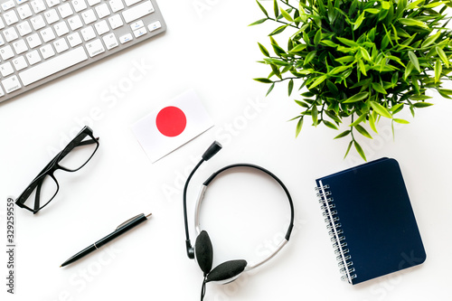 Fototapeta Learn Japanese online. Concept with flag, headset and keyboard on white background top-down obraz na płótnie