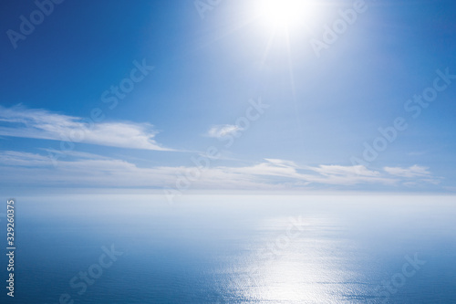 plakat An aerial view of eternal blue sea or ocean with sunny and cloudy sky.