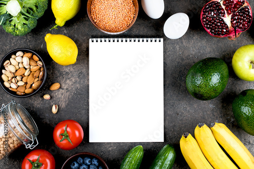 Fototapeta Food Mockup Recipe concept. Green vegetables, tomatoes, nuts, fruits, lentils, chickpeas, greens and empty notebook blank on grey concrete table. Flat lay, top view, copy space obraz