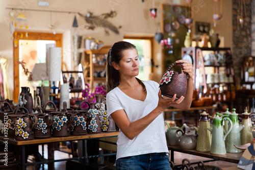 Fototapeta Female buyer chooses ceramic dishes and decorative items in a store obraz