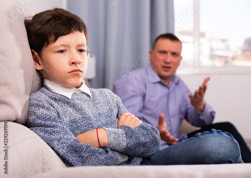 Offended boy and angry  father  having quarrel at home Wallpaper Mural