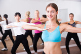 Group of active smiling people dancing together in dance studio