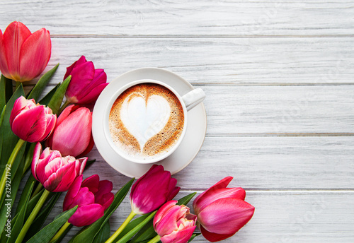 Coffee cup with latte art and pink tulips on the wood table Poster Mural XXL