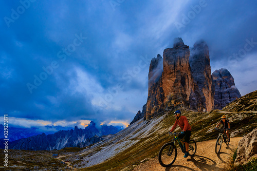 Fototapeta Cycling outdoor adventure in Dolomites. Cycling woman and man  on electric mountain bikes in Dolomites landscape. Couple cycling MTB enduro trail track. Outdoor sport activity. obraz