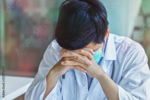 Photo Young man doctor in uniform has stress while sitting in his office, Emotional stress of overworked doctor